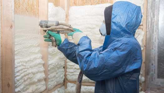 Masked worker applying spray insulation