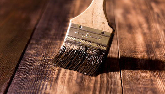 Up close image of a brush painting wood with a dark stain